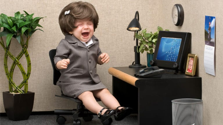 Crying baby in a salesperson's uniform and little cubicle