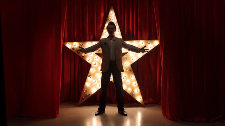 Man standing in front of a large lit up star on a stage
