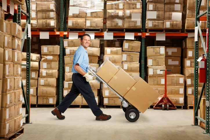 Warehouse worker pushing hand truck with boxes.