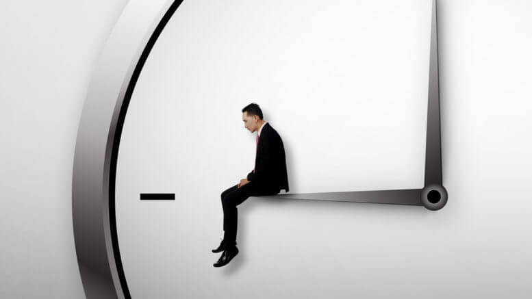 Small man in a suit sitting on a clock