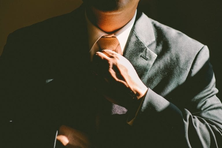 Man in suite and fixing his tie