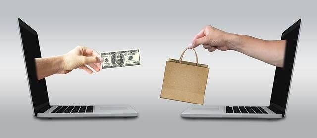Two laptops exchanging goods for money