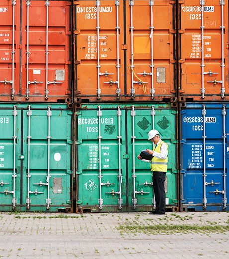 A workers stands in front of cargo containers