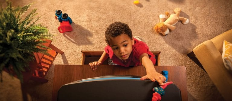 Child reaching for a toy on top of a dresser