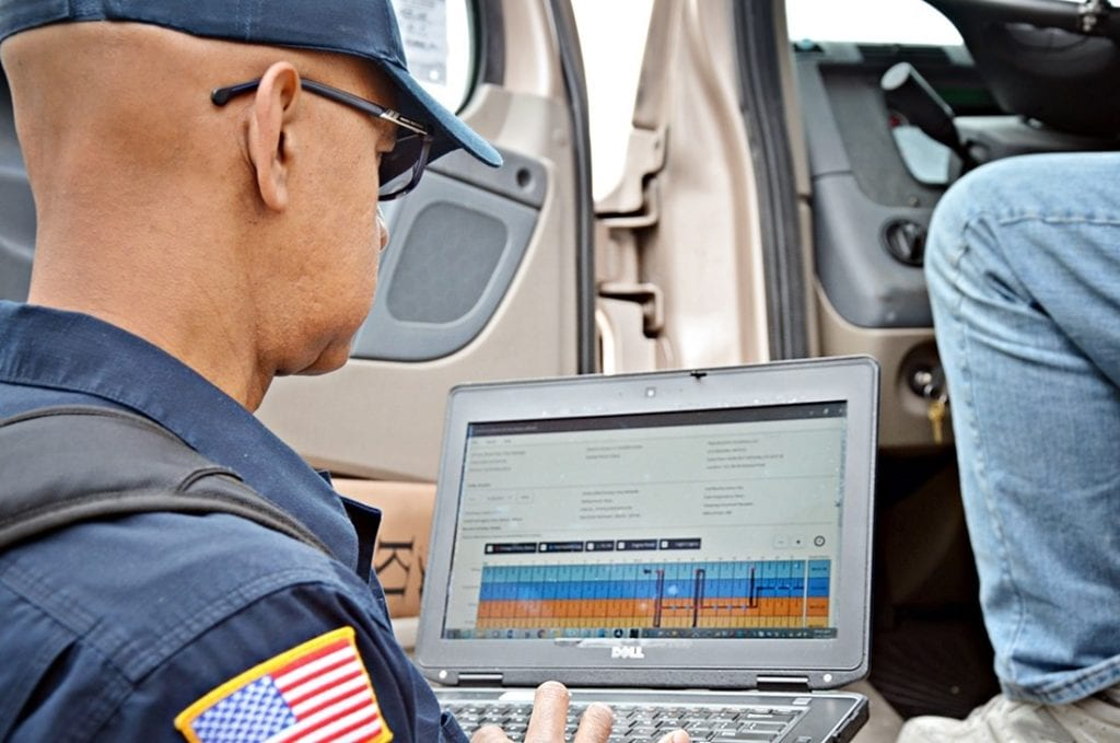 A truck driver records his hours on an electronic logging device