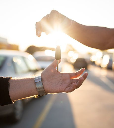 Person handing another person keys to a car