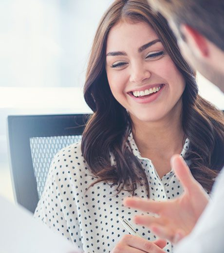Woman smiling while talking with sales person