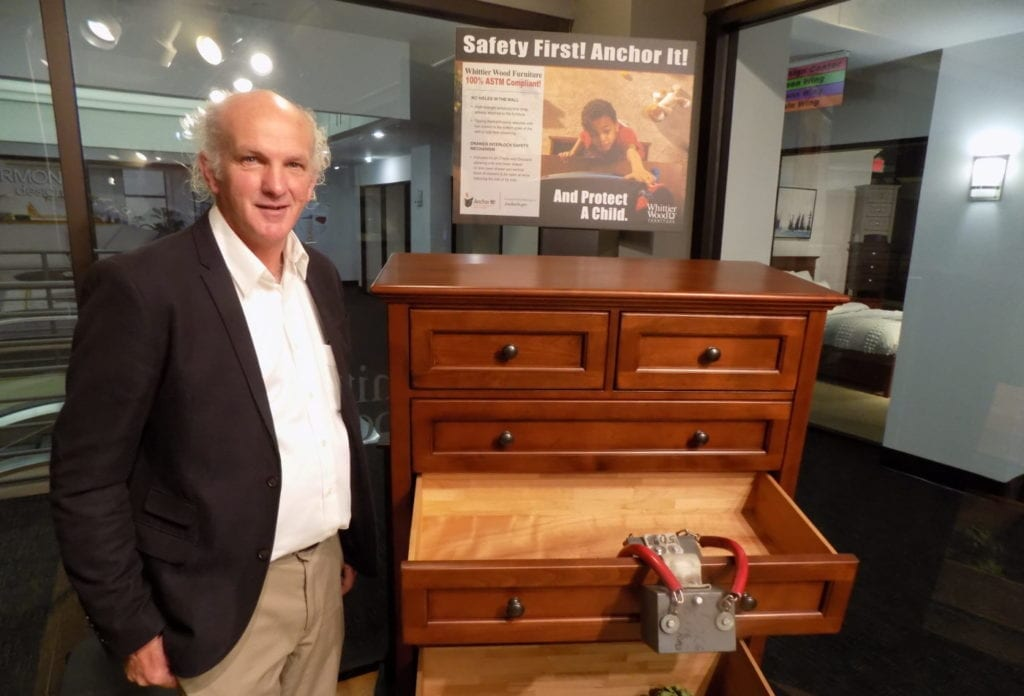 Photo shows Scott Whittier with a dresser with demonstration weight