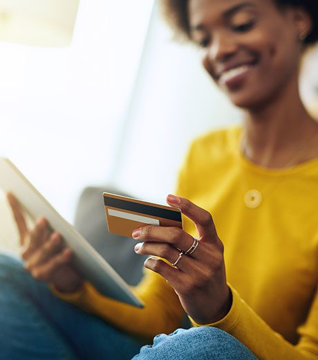 Photo of African American woman holding a payment card and a tablet.