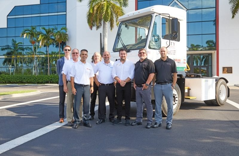 Photo shows Andrew Koenig and other men in front of a City Furniture truck