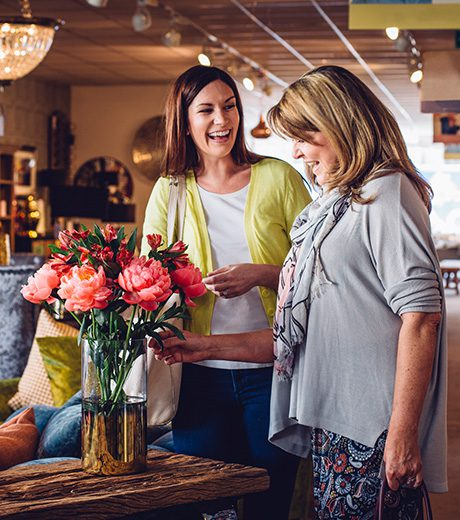 Woman helping another woman look for something in a furniture store