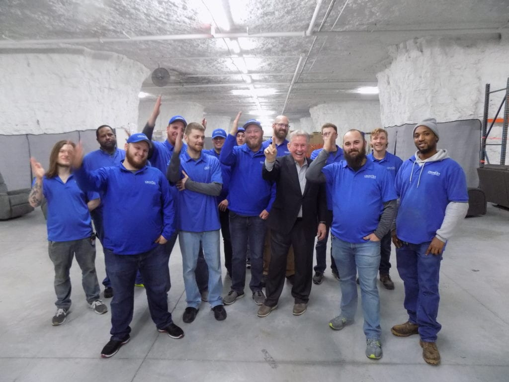 Photo shows Greg Crowley surrounded by workers in his warehouse