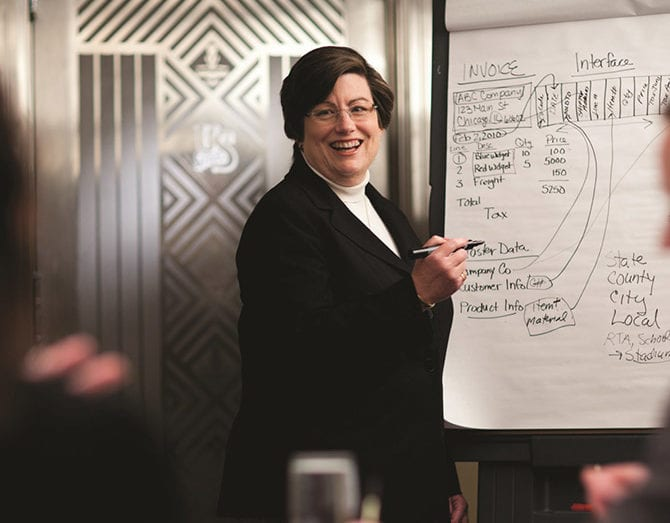 Photo shows a woman at a white board