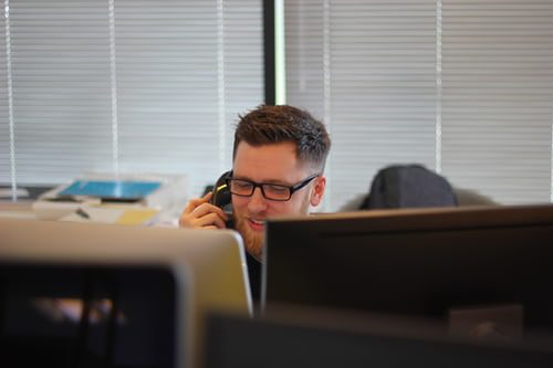 photo shows a man in an office making a phone call