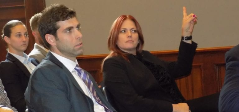 Image shows a man and woman in a meeting room