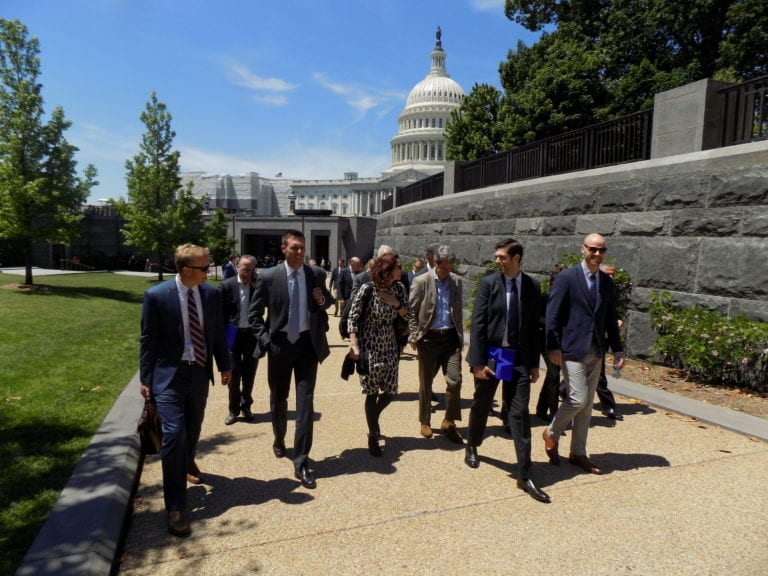 Photo shows a group of people walking with the U.S. Capitol in the background
