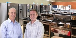 Image shows two men in the appliances section of their store