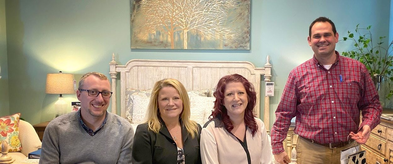 Photo shows four people in a furniture showroom