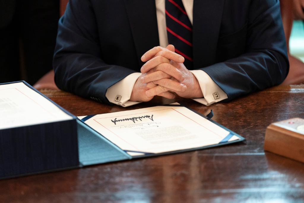image shows the president's hands and a signed bill