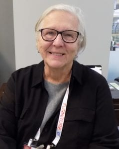 Image shows a woman with glasses and white hair
