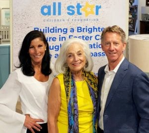 Image shows three people in from of a banner for the All Star Children's Foundation