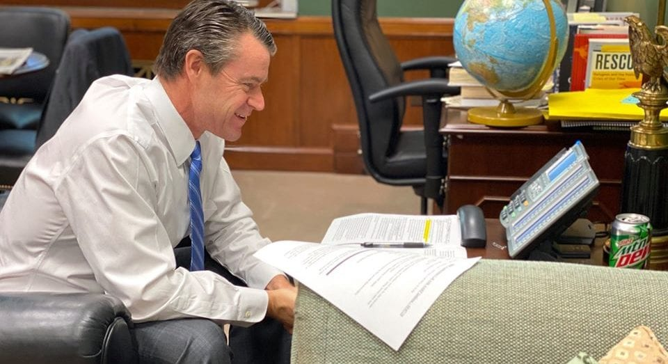 Image shows a man sitting in an office