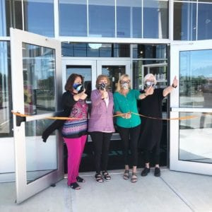 Image shows four women wearing masks outside a furniture store