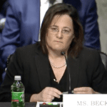 Image shows a woman sitting at a hearing table