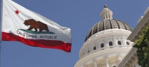 Image shows the California state flag flying in front of the capitol dome