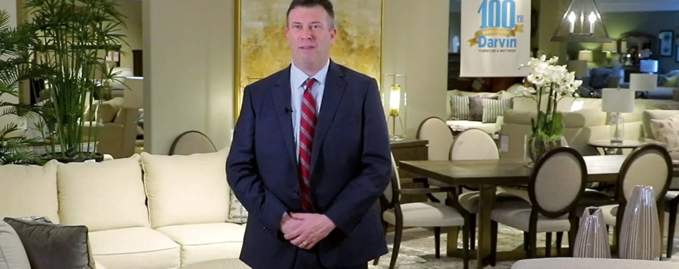 Image shows a man wearing coat and tie standing in a furniture showroom