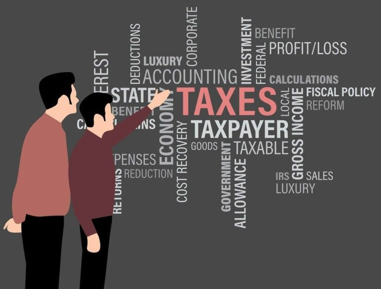 Image shows a graphic of two people are a wall of tax terms