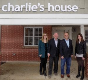 Image shows four people standing in front of Charlie's House