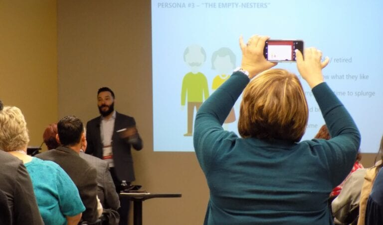 Image shows a woman holding a phone to take a photograph in a seminar room