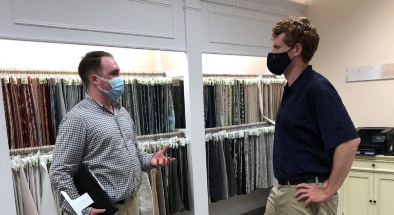 Image shows two men wearing face coverings