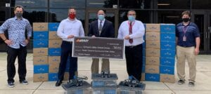 Image shows a check presentation outside a school.