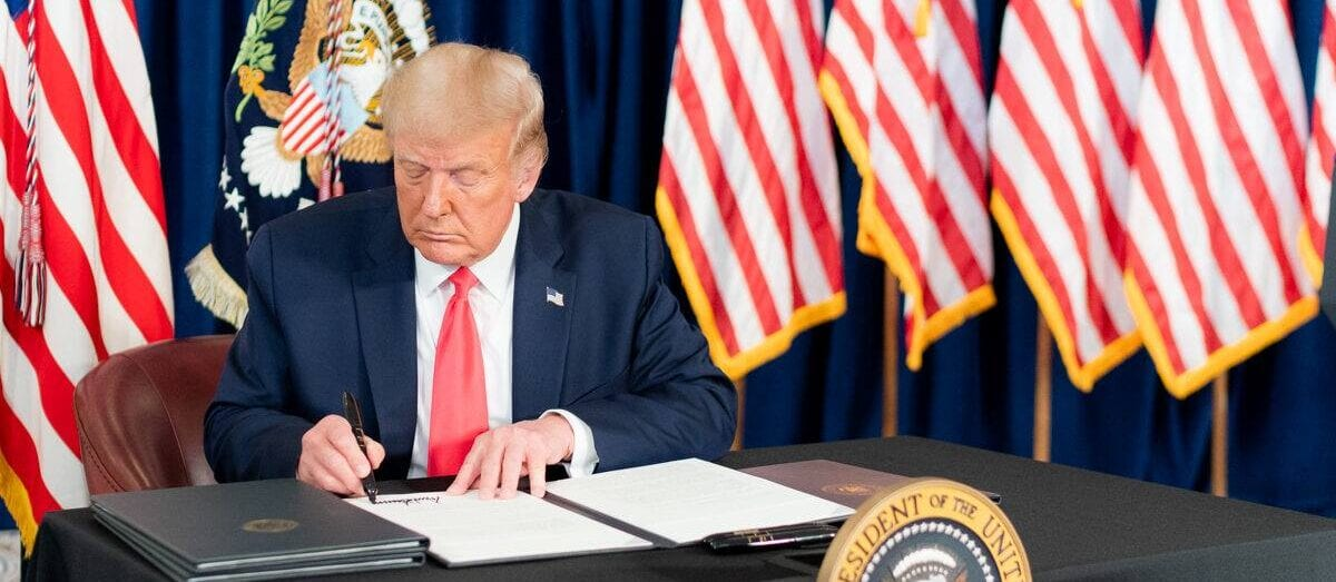 Image shows the president signing a paper