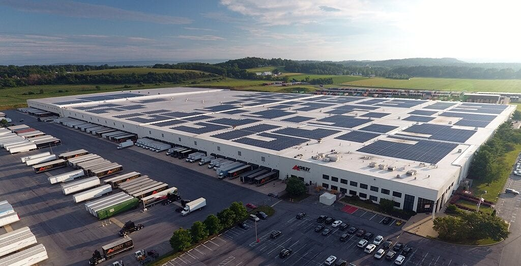 Image shows an industrial facility with solar panels on its roof