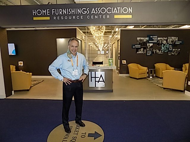 Image shows a man standing in front of a furniture showroom