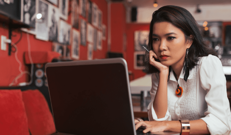 Image shows a woman looking intently at a laptop screen