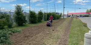 Image shows a man plowing a field