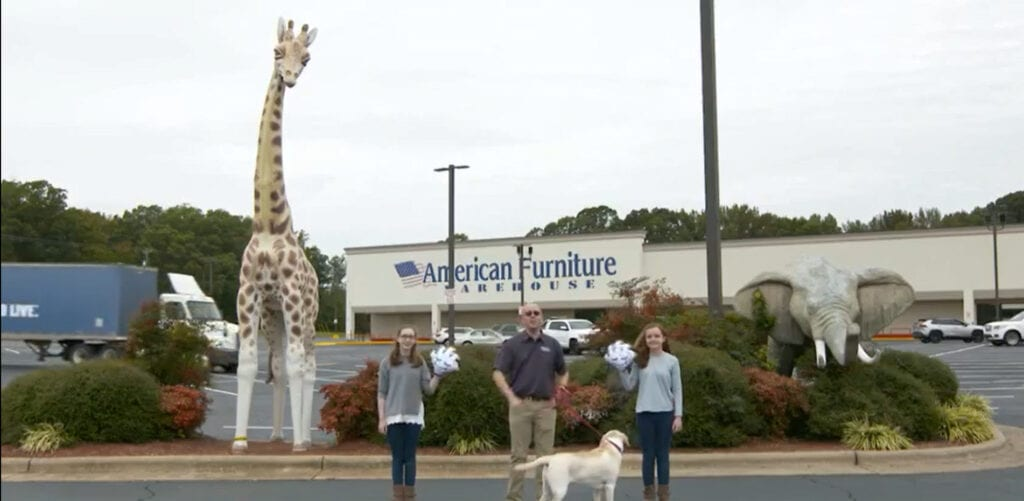 A man and two girls outside a furniture store