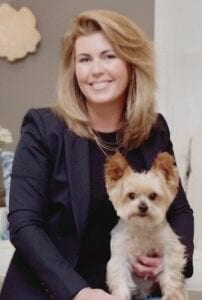 Image shows a woman holding a dog