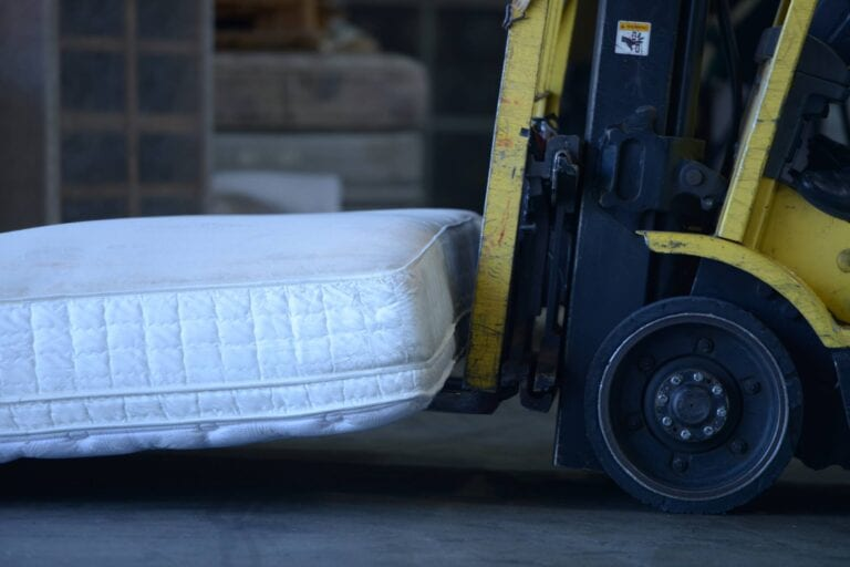 Image shows a forklift carrying a mattress