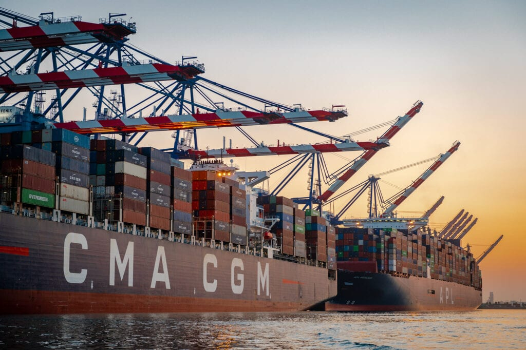 Image shows container ships and cranes