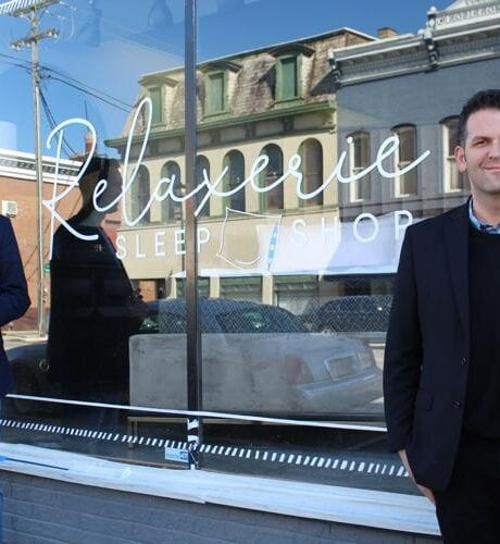 Photo of owners outside store.