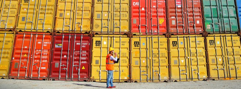 Man standing in front of a wall of cargo containers